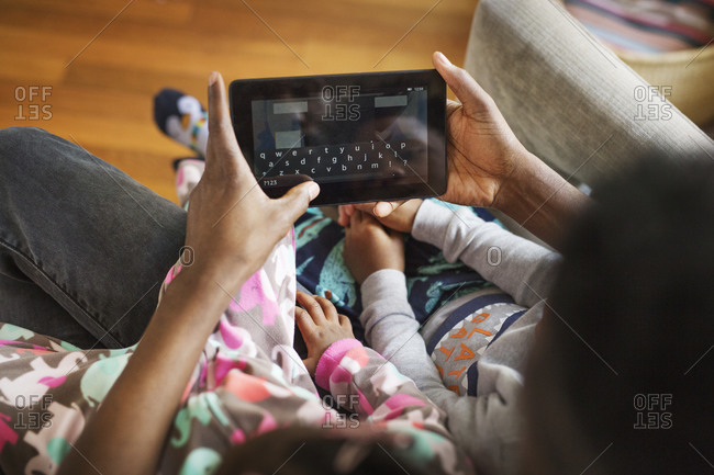 High angle view of father and his kids playing on a tablet together