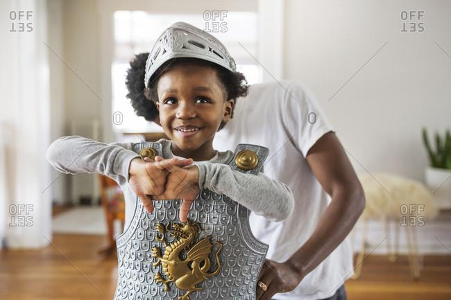 Little boy getting dressed in pretend armor