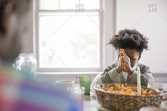 Boy saying prayers at the dinner table