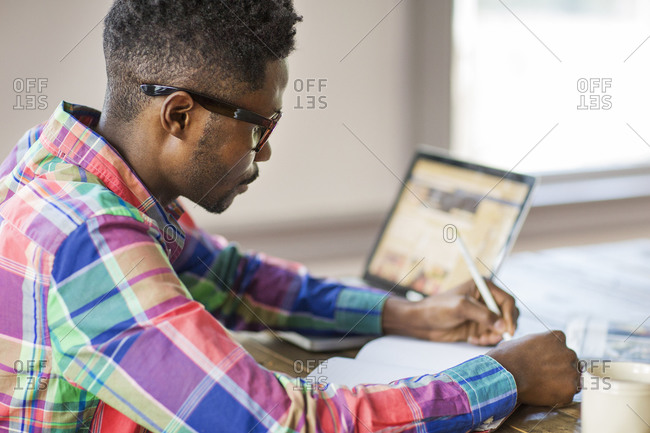 Man using a laptop and writing in a notebook