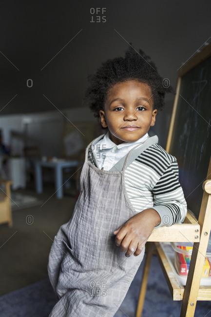 Portrait of a little boy leaning on a chalkboard