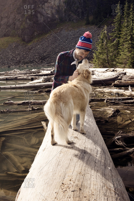Man on a log with his dog in the wilderness