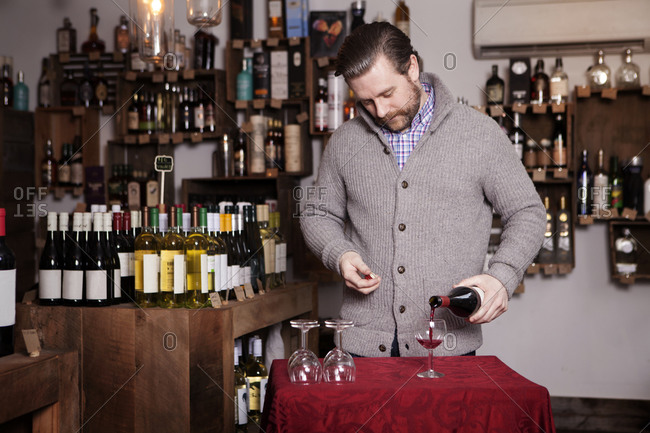 Man pouring glass of wine in a wine store