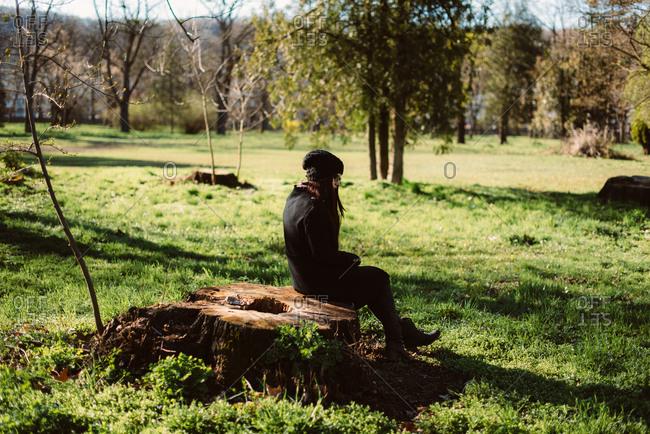 Woman resting on stump