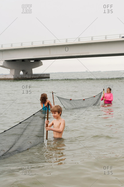 Children in ocean holding fishing nets and Sanibel causeway bridge, Sanibel Island, Pine Island Sound, Florida, USA