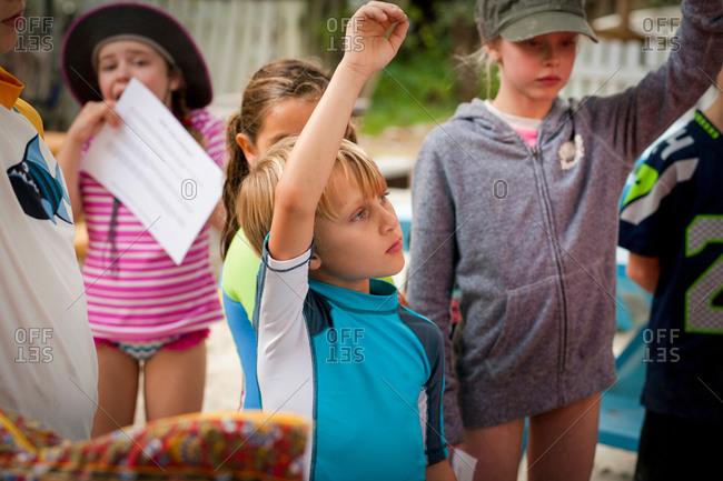 Children wearing swimwear hands raised to answer question