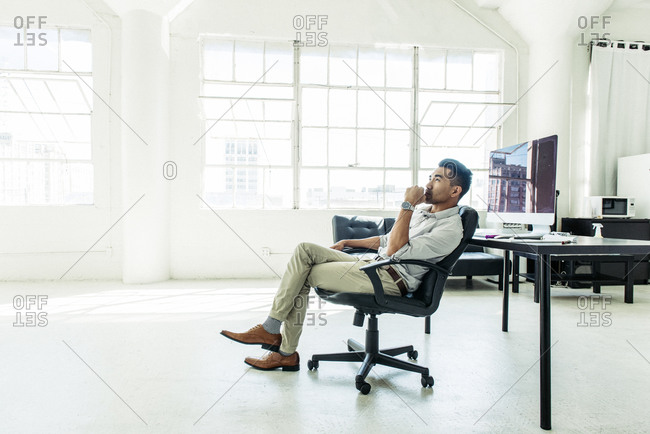 Businessman contemplating by office window