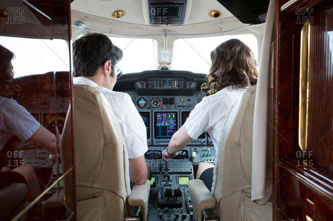 Rear view of male and female pilots in cockpit of private jet