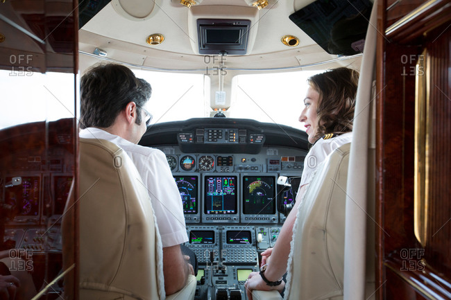 Rear view of male and female pilots talking in cockpit of private jet