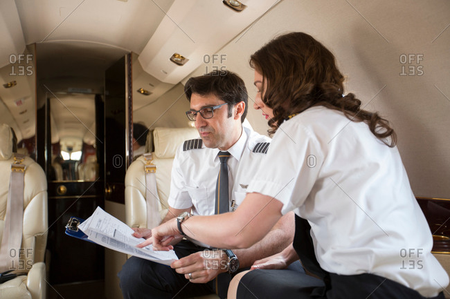 Male and female pilots reading flight plan in cabin of private jet