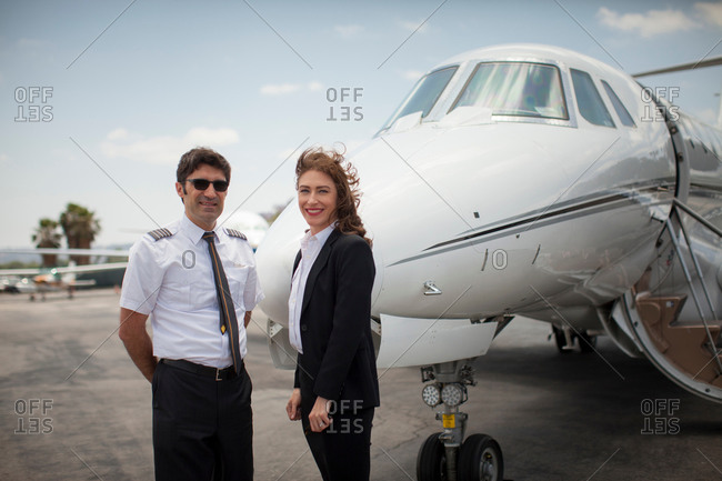 Portrait of female businesswoman and pilot of private jet at airport