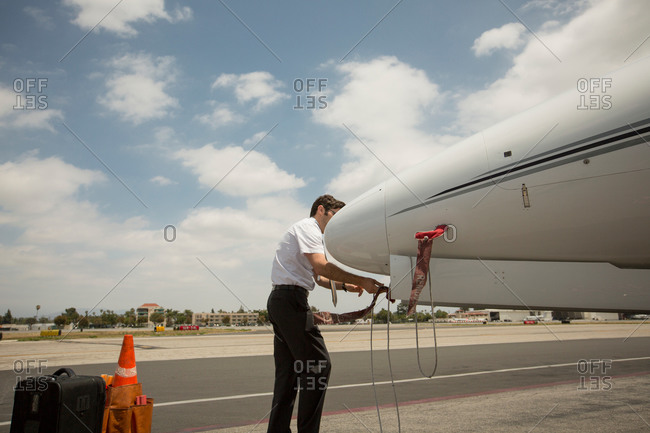 Male private jet pilot checking plane at airport