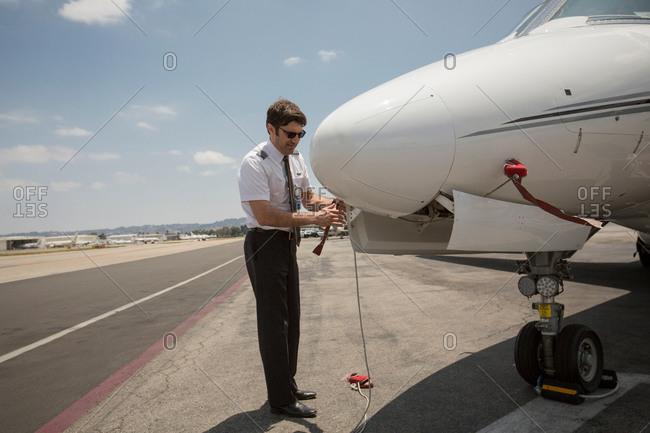 Male private jet pilot preparing plane at airport