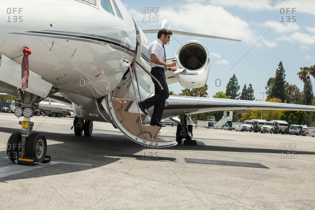 Male private jet pilot stepping from plane at airport