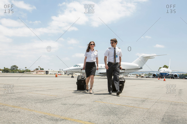Male and female private jet pilots pulling wheeled suitcases at airport