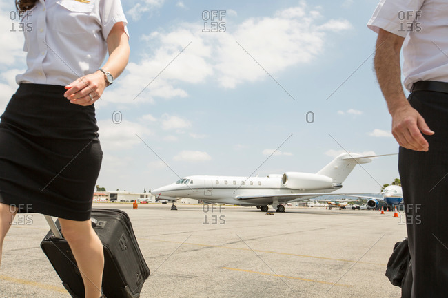 Cropped shot of male and female private jet pilots pulling wheeled suitcases at airport