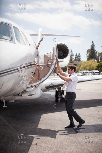 Male private jet pilot closing plane door at airport
