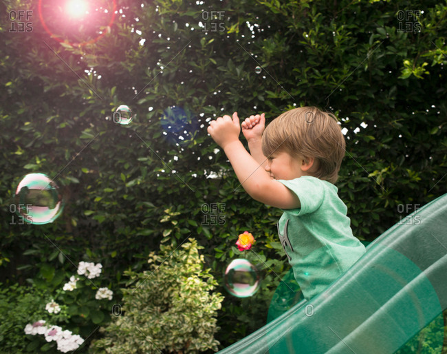 Young boy sliding down garden slide