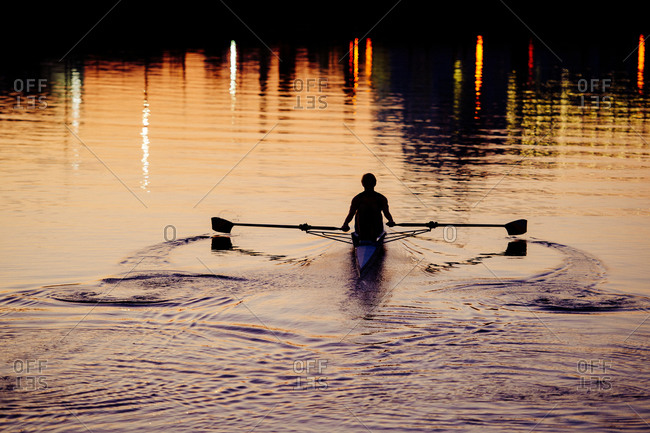 Silhouette of a young man rowing on river at sunset