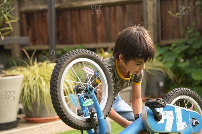 Boy in garden repairing upside down bicycle looking down