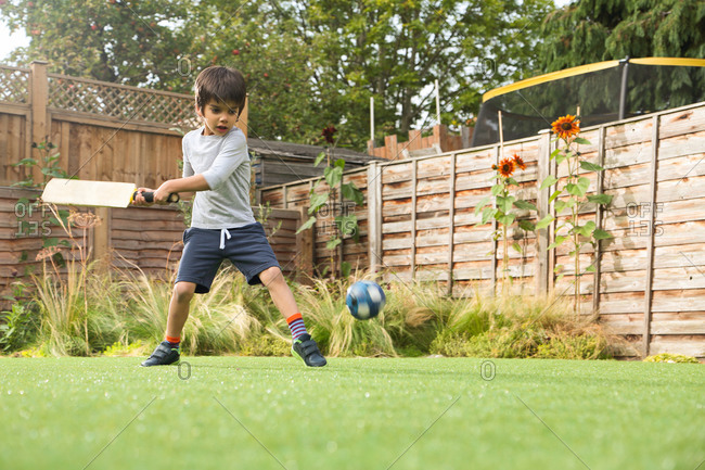 Boy playing cricket in garden with ball in mid air