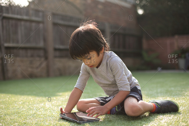 Boy in garden sitting on grass looking down using digital tablet