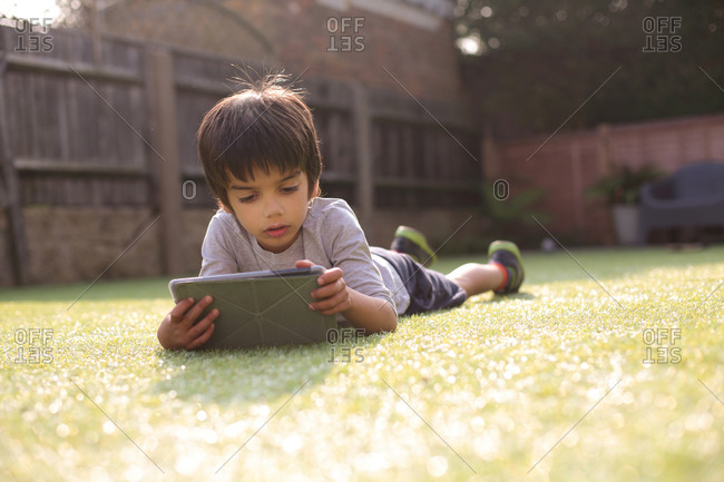 Boy in garden lying on front on grass looking down using digital tablet