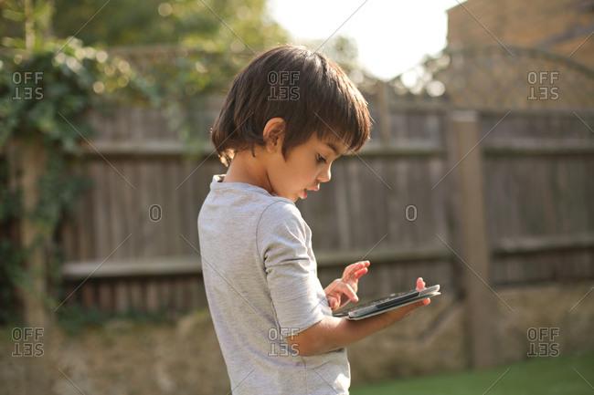 Side view of boy in garden looking down using digital tablet