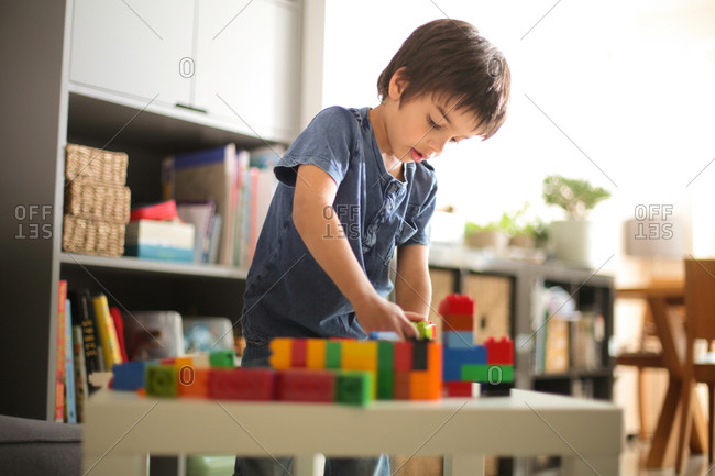 Boy at home looking down playing with colorful building blocks