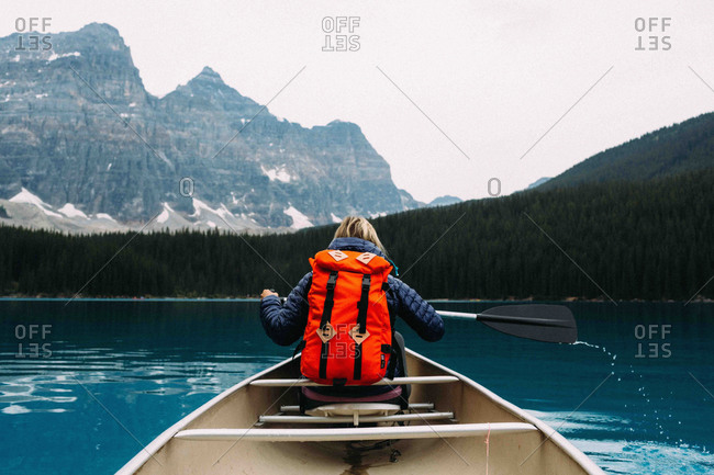 Rear view of mid adult woman paddling canoe, Moraine lake, Banff National Park, Alberta Canada