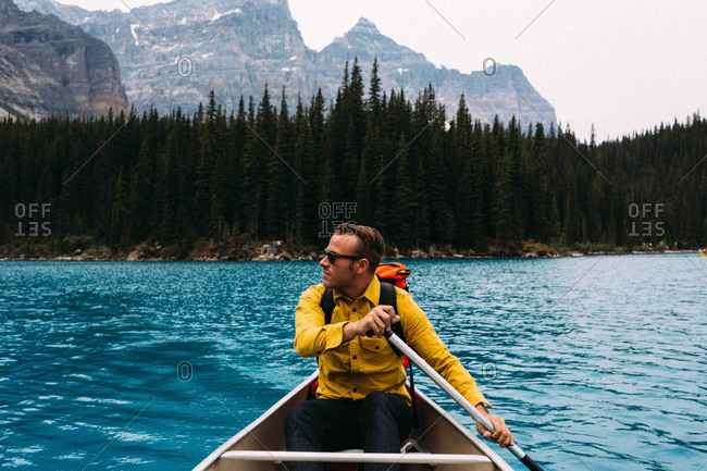 Front view of mid adult man paddling canoe, looking away, Moraine lake, Banff National Park, Alberta Canada