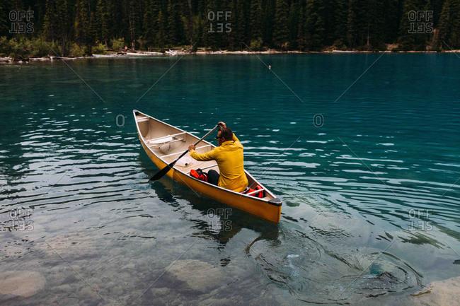 High angle rear view of mid adult man paddling canoe on Moraine lake, Banff National Park, Alberta Canada