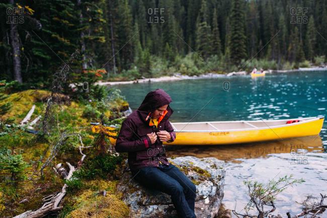 Mid adult man sitting by canoe on Moraine lake, looking down fastening waterproof coat, Banff National Park, Alberta Canada