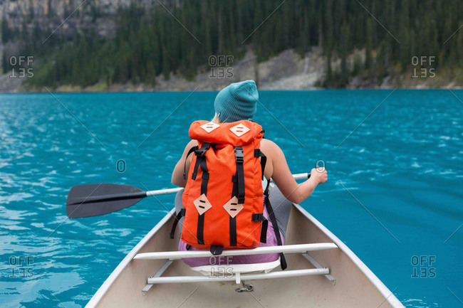 Rear view of mid adult woman with orange color backpack paddling canoe, Moraine lake, Banff National Park, Alberta Canada