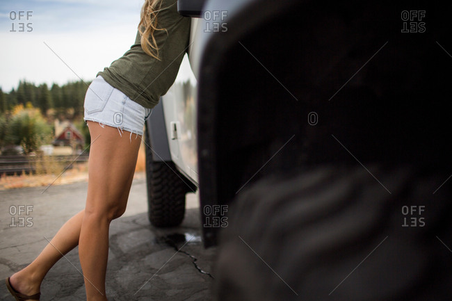 Neck down view of young woman in shorts leaning forward on suv