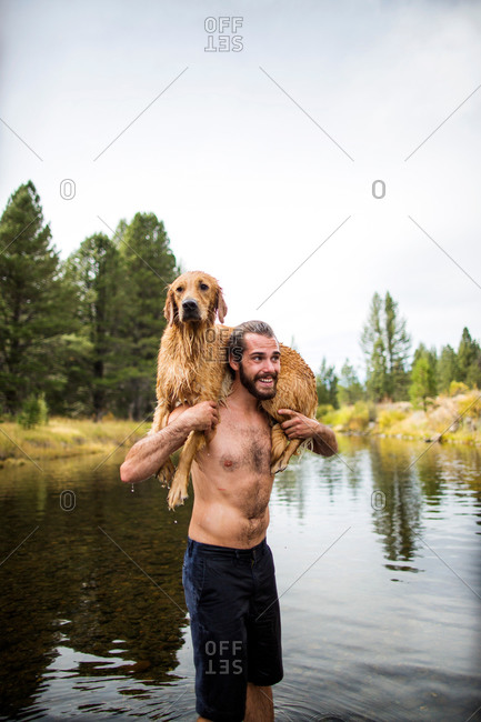 Young man carrying wet dog over shoulders in river, Lake Tahoe, Nevada, USA
