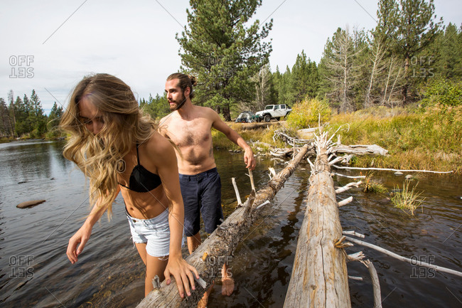 Young couple crossing river, Lake Tahoe, Nevada, USA