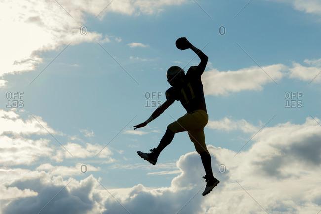 Teenage football player jumping with ball