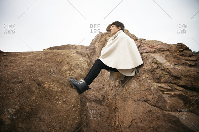 Woman wearing a coat cape sitting on a rocky outcropping