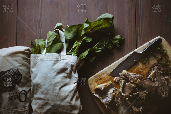 Overhead view of a cutting board covered with lamb and two white tote bags filled with fresh greens