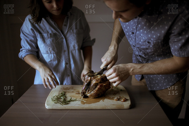 Couple cutting a portion of lamb on a cutting board