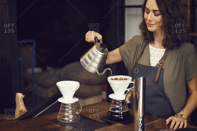 Woman making a cup of pour over coffee in a coffee shop