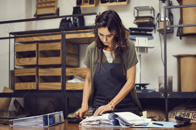 Woman standing by a desk while reviewing business files