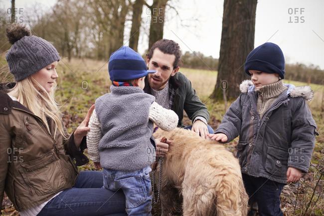 Family petting dog on winter walk
