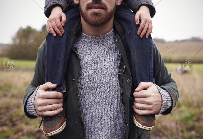 Close up of father gives son ride on shoulders during walk