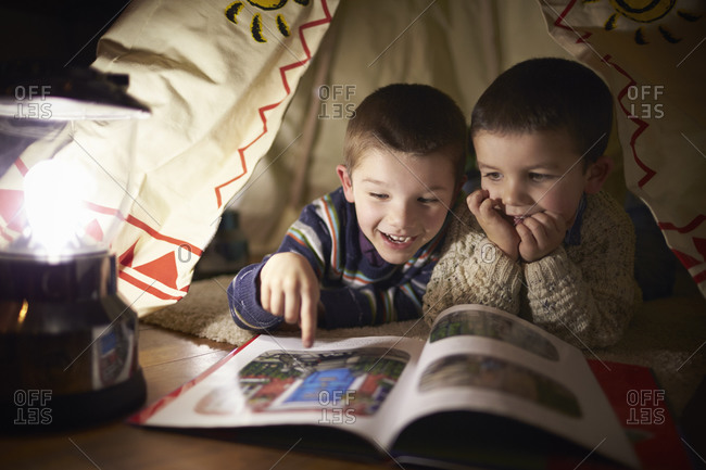 Two brothers reading inside tent set up indoors stock photo