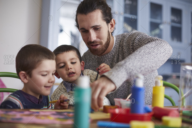 Father and sons paint picture at kitchen table