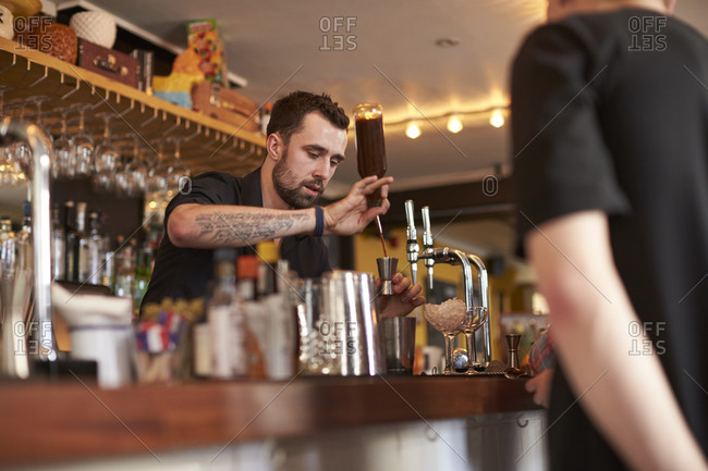 Bartender measure out liquor during a  cocktail making lesson