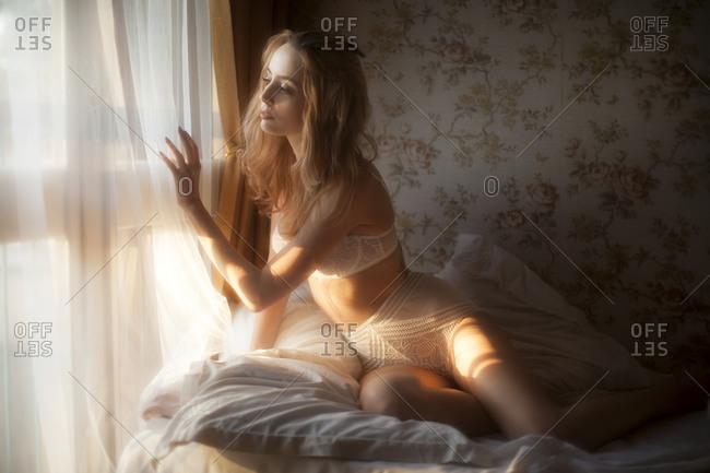 Woman wearing bra and panties looking through the window of her bedroom