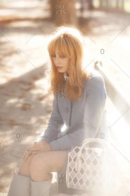 Woman sitting on a city park bench bathed in autumn light